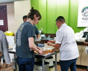Photo of UNYA's Mentorship Program mentors and youth making a meal together with Chef Heat Leliberte.