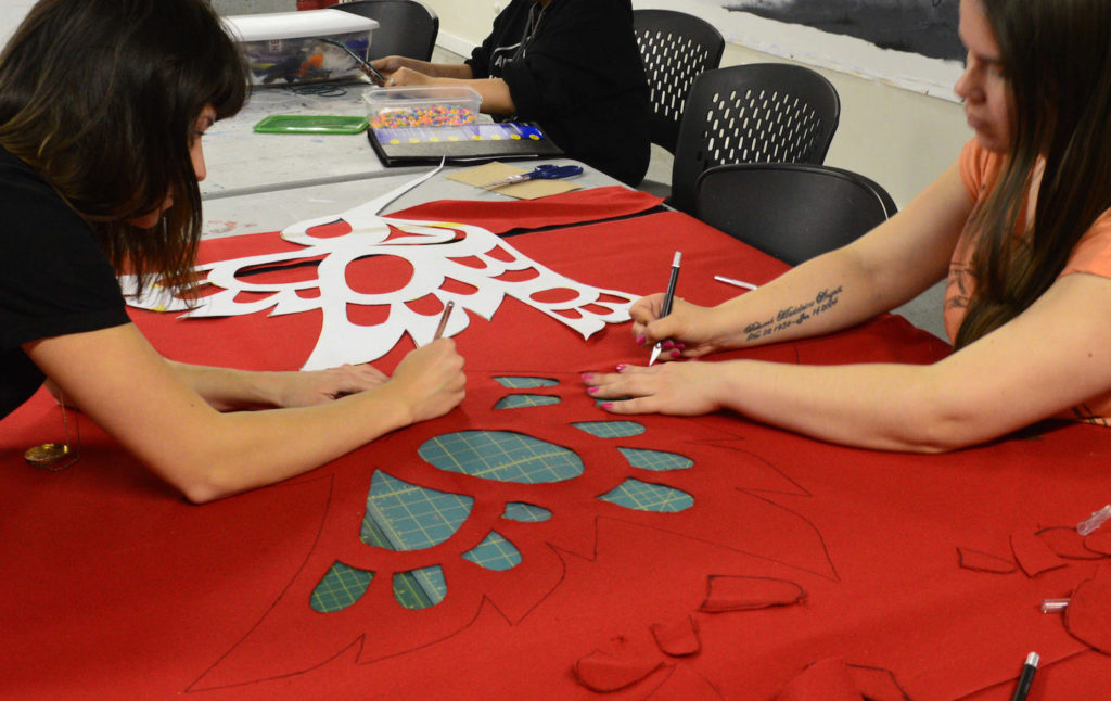 Indigenous youth making a button blanket in Urban Native Youth Association's Overly Creative Minds studio.