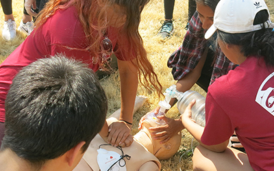 Photo of students at the Justice Institute of BC Indigenous youth career camp practice their CPR skills on a training mannequin