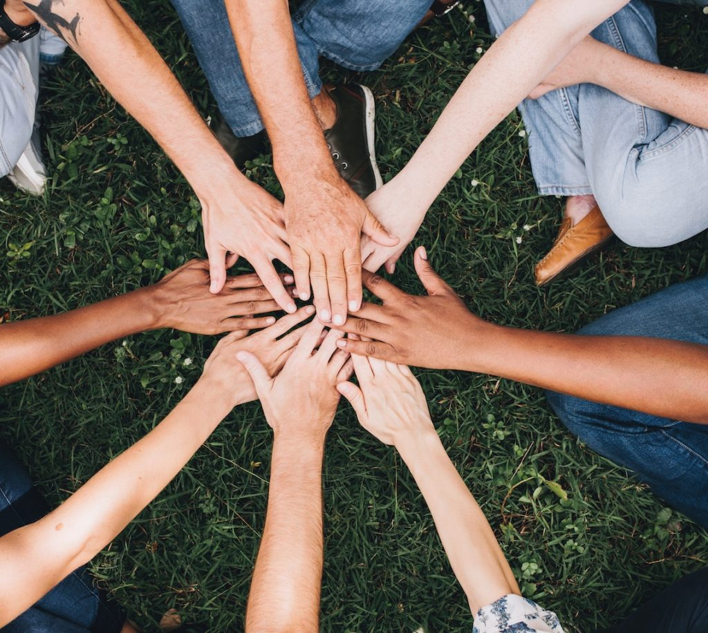 Photo of a group huddle, hands together in a circle