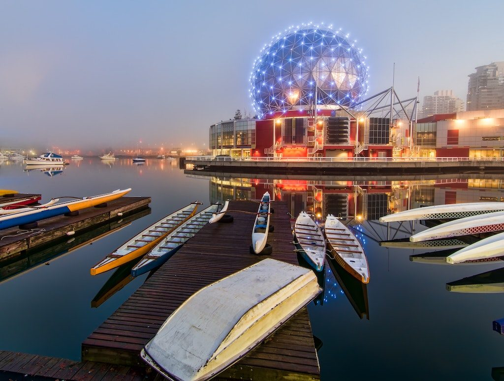 Boats docked in False Creek with Science World in the background.