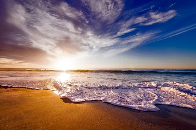 Photo of a summer sunset over the beach with waves washing over the sand.